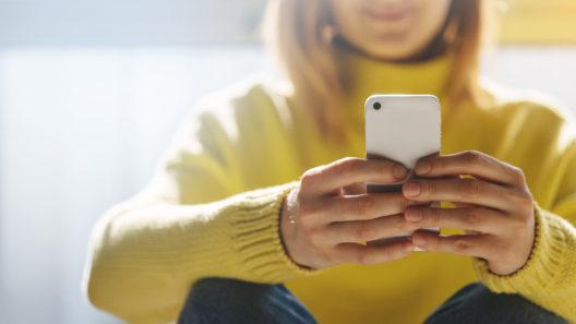 Kvinna håller i en mobiltelefon