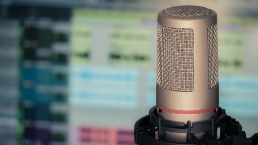 En mikrofon framför skärm med ljudbearbetingsprogram