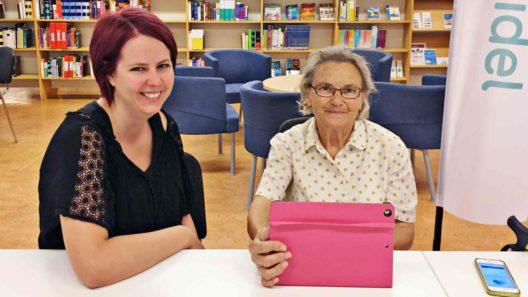 Två personer sitter vid ett bord. Emelie handleder Gunilla, 90 år.