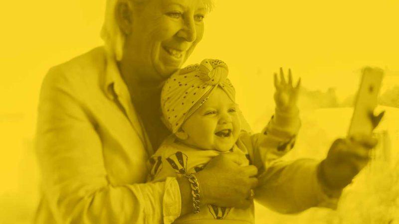 En senior, kanske en mor- eller farförälder, tar selfie med spädbarn