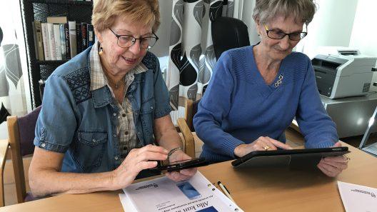 På bilden sitter två besökare hos Digidel Senior i Borås och utforskar sina tekniska prylar.