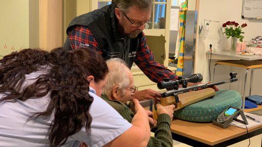 Em äldre man sitter vid ett bord och skjuter med en bössa. Han får hjälp av två personer.