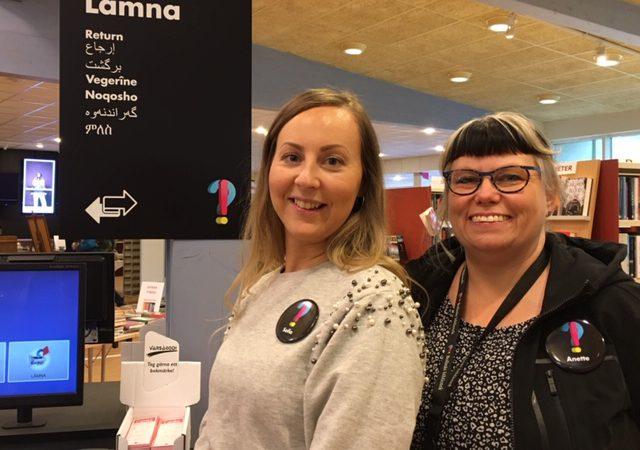 """Bibliotekarierna Sofia Eliasson och Anette Helgesson på Bollnäs bibliote, framför en skylt sär det står """"lämna"""" på svenska och sju andra språk."""