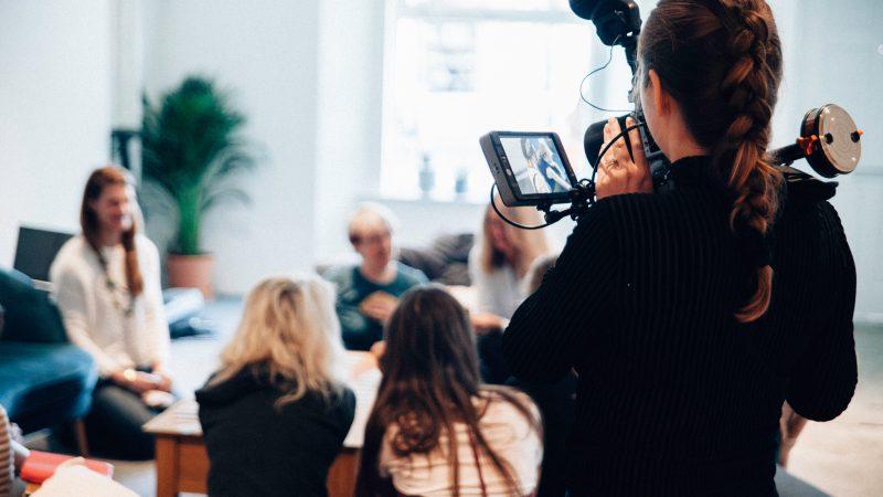 En kvinna videofilmar en grupp