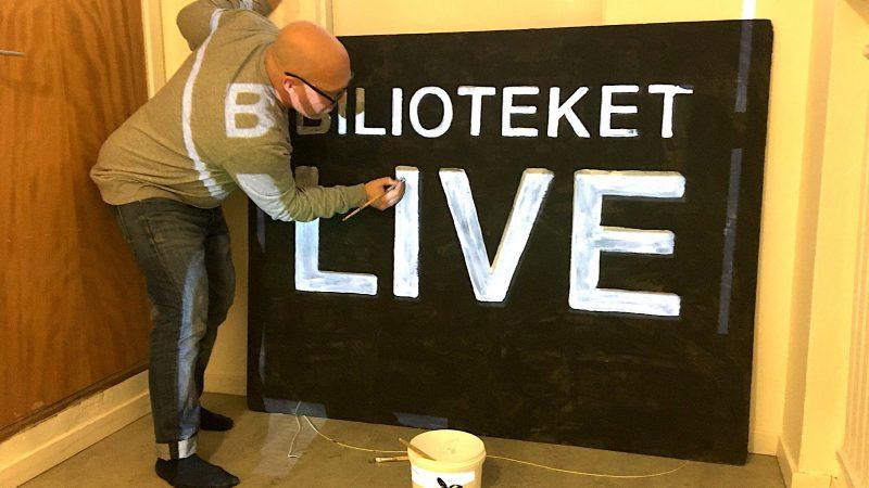 """En man målar en skylt med texten """"bibliotek live""""."""