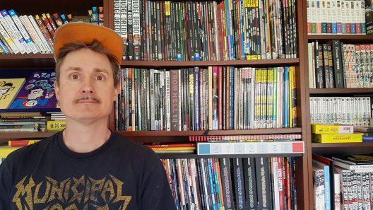 Ola Nilsson står framför en bokhylla. Han har en keps på sig.